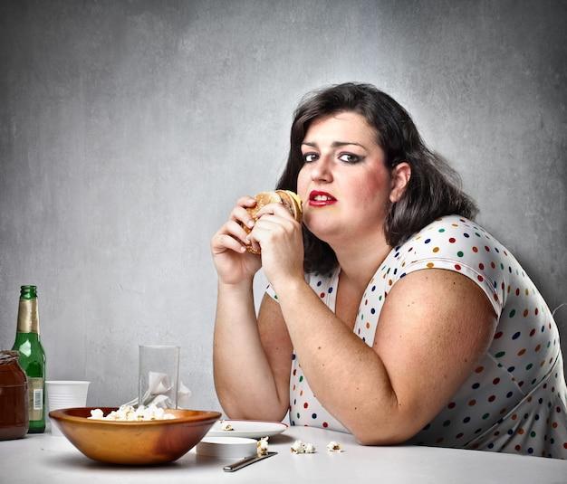 Donna grassa che mangia hamburger