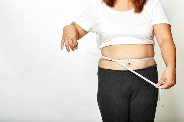 Donna grassa con nastro adesivo di misura