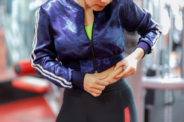 Donna grassa, mano di donna obesa che tiene il grasso della pancia in eccesso, pancia grassa in sovrappeso della donna, concetto di stile di vita di dieta della donna per ridurre la pancia e modellare il muscolo dello stomaco sano.