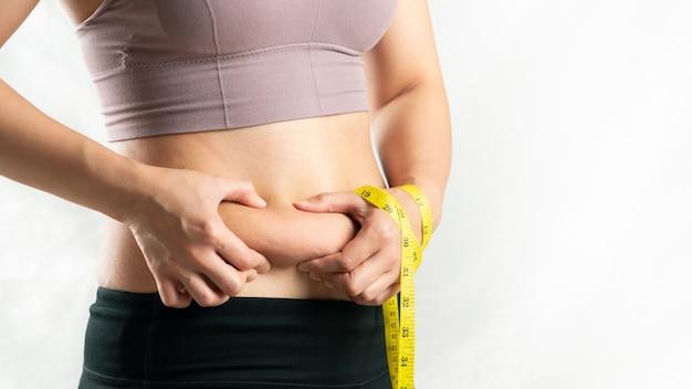 Donna grassa, pancia grassa, paffuto, mano obesa della donna che tiene grasso in eccesso della pancia con nastro adesivo di misura