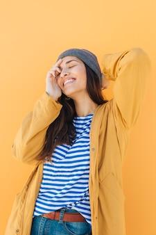 Donna graziosa allegra che posa portando il cappello a maglia con gli occhi chiusi