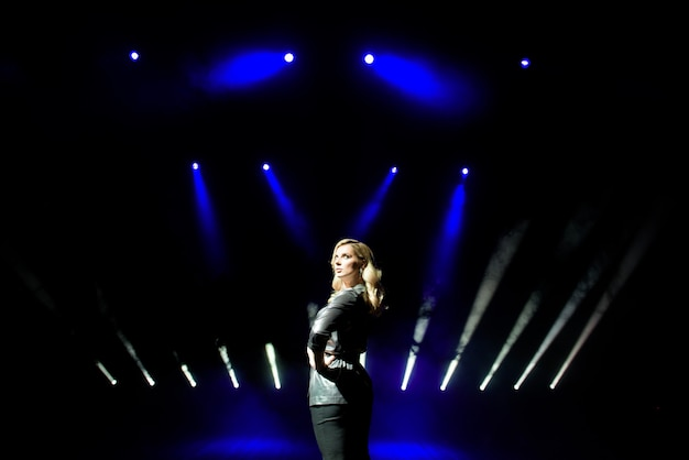 Donna graziosa artista sullo sfondo di faretti sfocati sul palco