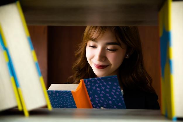 Donna graziosa asiatica in biblioteca