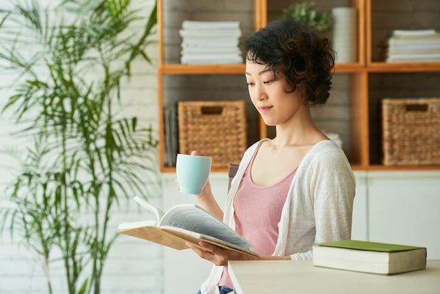 Donna graziosa avvolta nella lettura