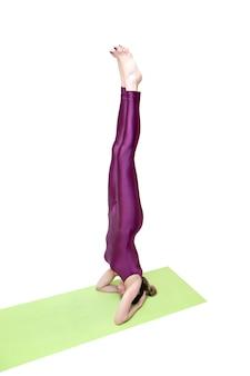 Donna graziosa calma che fa esercitazione di yoga isolata su priorità bassa bianca