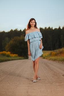 Donna graziosa che cammina sulla strada campestre nel tramonto