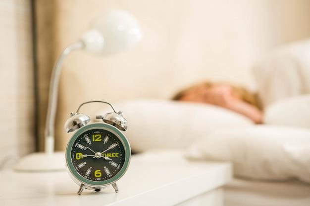 Donna graziosa che dorme con la vista della sveglia nella camera da letto