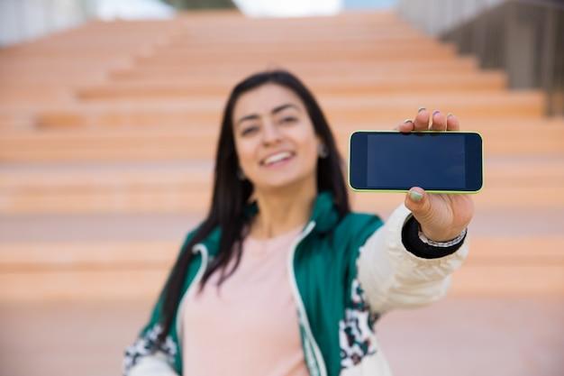 Donna graziosa che fa selfie sul telefono, sorridente. gadget a fuoco