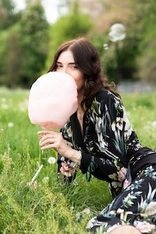 Donna graziosa che gode dello zucchero filato