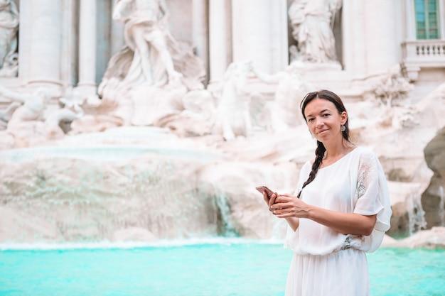 Donna graziosa che guarda alla fontana di trevi durante il suo viaggio a roma, italia,