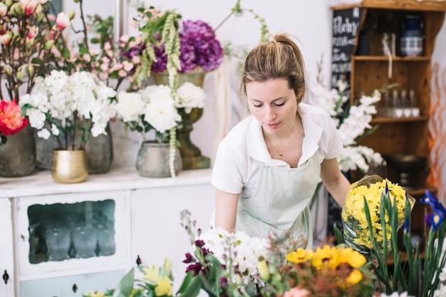 Donna graziosa che lavora nel negozio di fiori