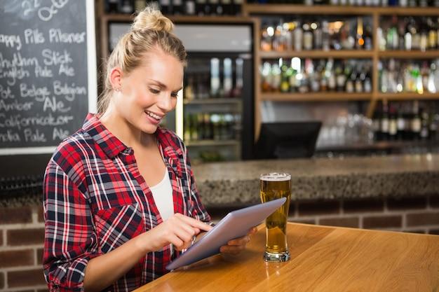 Donna graziosa che mangia una birra e che esamina compressa