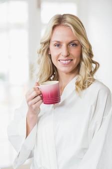 Donna graziosa che mangia una tazza di caffè nella cucina