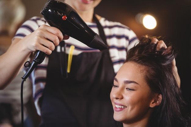 Donna graziosa che ottiene i suoi capelli asciugati