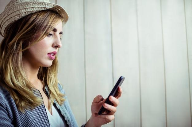 Donna graziosa che per mezzo dello smartphone