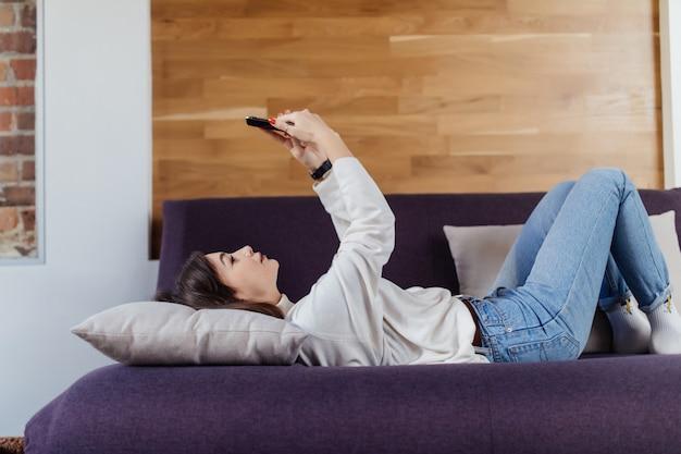 Donna graziosa che per mezzo di uno smart phone che si trova su un letto a casa