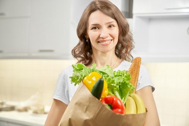 Donna graziosa che posa con il sacco di carta pieno delle verdure.