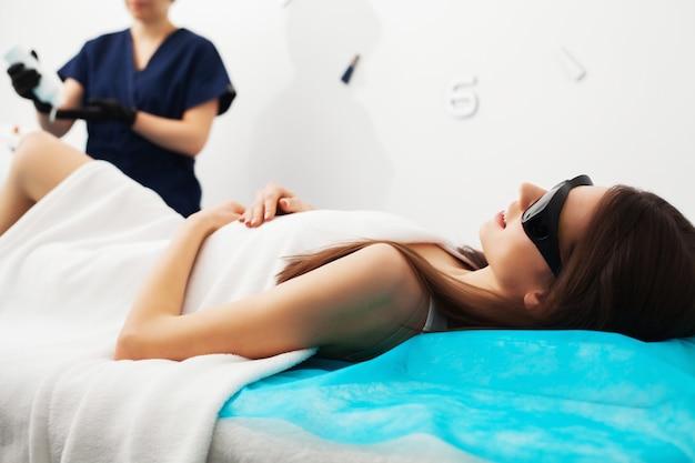 Donna graziosa che riceve servizio di depilazione del laser nel salone di bellezza