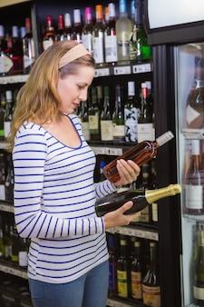 Donna graziosa che sceglie bottiglia di vino