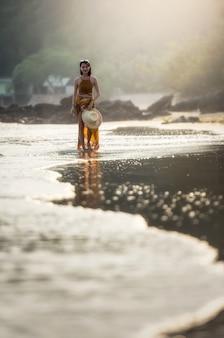 Donna graziosa che si distende alla spiaggia tropicale. spiagge e paesi tropicali lontani. concetto di viaggio.
