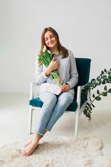 Donna graziosa che si siede con i tulipani e la cartolina d'auguri