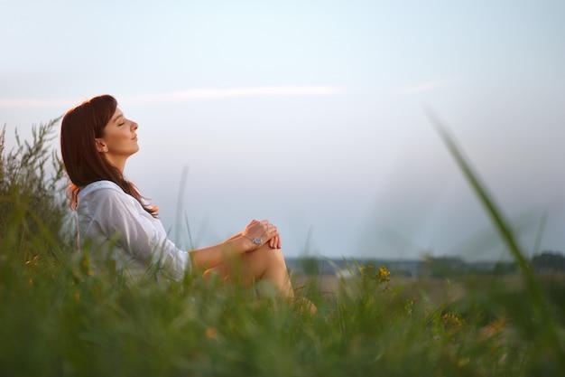Donna graziosa che si siede dal bordo della strada campestre sul tramonto