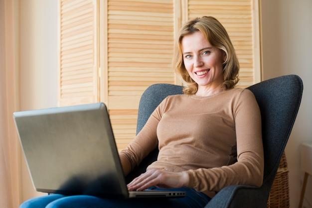 Donna graziosa che si siede e che per mezzo del computer portatile