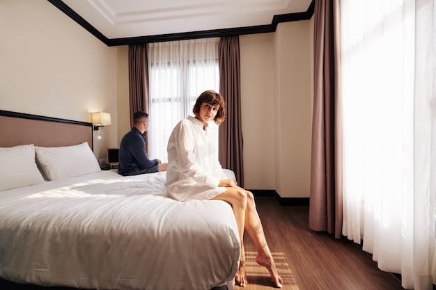 Donna graziosa che si siede sul letto dell'hotel