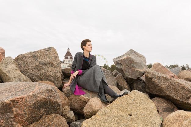 Donna graziosa che si siede sulle pietre in un costume grigio della gonna un giorno nuvoloso e che osserva da parte.