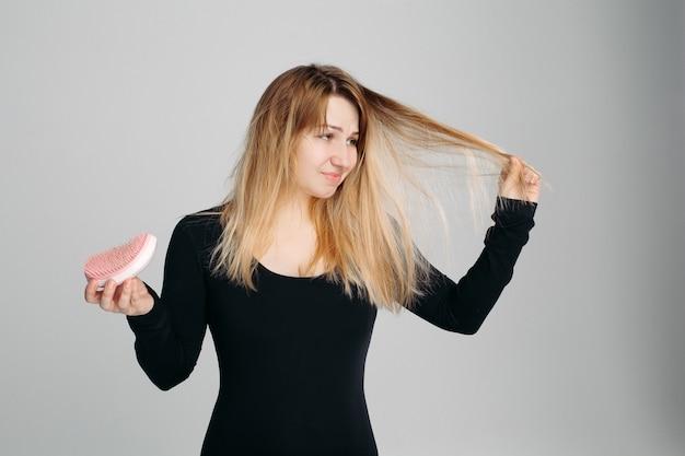 Donna graziosa che tiene capelli disordinati in una mano e spazzola per capelli in un'altra