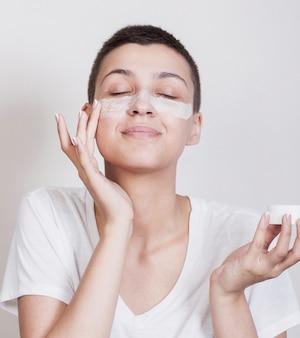 Donna graziosa che usando una crema per la pelle