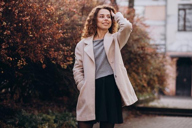 Donna graziosa con capelli ricci che cammina in un cappotto di autunno