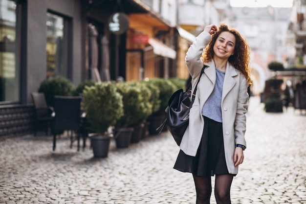 Donna graziosa con capelli ricci che cammina in una strada del caffè
