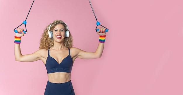Donna graziosa con ginnastica di pratica dei capelli biondi e forma fisica che ascolta la musica con le cuffie