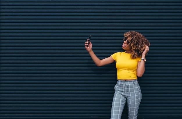 Donna graziosa con i capelli afro che per mezzo del telefono cellulare.