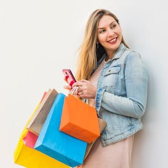 Donna graziosa con i sacchetti della spesa luminosi facendo uso dello smartphone