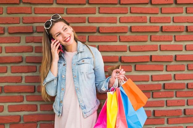 Donna graziosa con i sacchetti della spesa variopinti che parla dal telefono al muro di mattoni