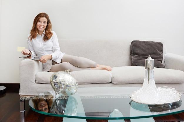 Donna graziosa con il computer portatile sul sofà