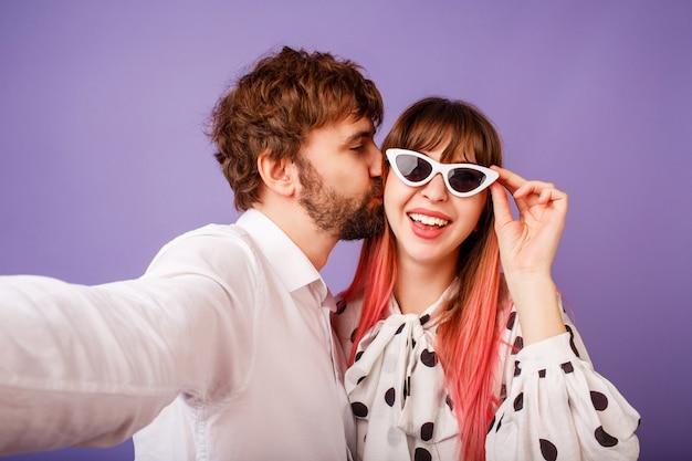 Donna graziosa con il sorriso schietto e capelli rosa che posano con il suo ragazzo con la barba