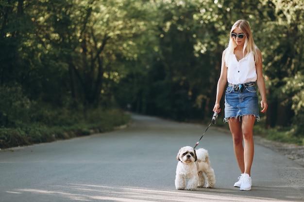 Donna graziosa con il suo cane fuori nel parco