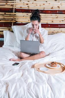 Donna graziosa con il telefono e il computer portatile a letto