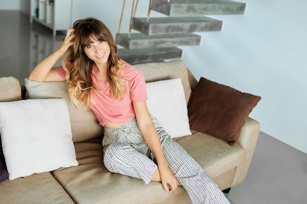 Donna graziosa con l'acconciatura ondulata che si rilassa sul sofà accogliente in salone