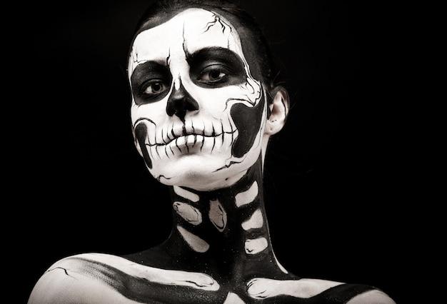 Donna graziosa con la pittura di scheletro del corpo