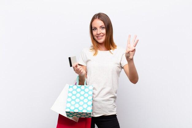 Donna graziosa con la testa rossa che sorride e sembra amichevole, mostrando il numero tre o terzo con la mano in avanti, contando con le borse della spesa