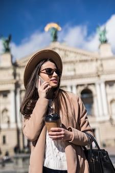Donna graziosa con le parentesi graffe in occhiali da sole in posa in abiti casual in città