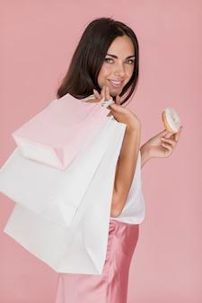 Donna graziosa con una ciambella su uno sfondo rosa