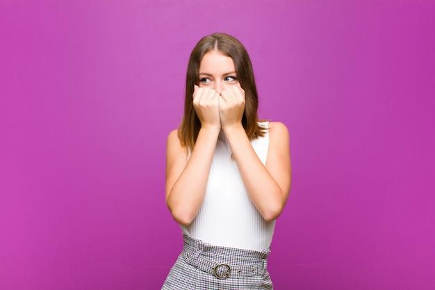 Donna graziosa dalla testa rossa che sembra preoccupata, ansiosa, stressata e spaventata, mordendosi le unghie e cercando di copiare lo spazio laterale contro il muro viola