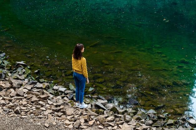 Donna graziosa del brunette che gode del lanscape delle montagne, levantesi in piedi vicino al lago