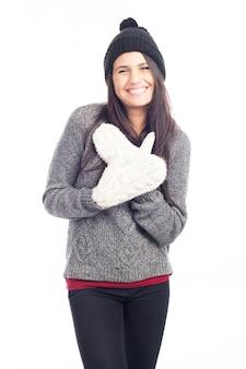 Donna graziosa del brunette con un cappello di lana un maglione e guanti che sorridono e allegri