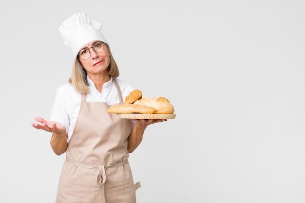 Donna graziosa del panettiere di medio evo con pane contro la parete dello spazio della copia